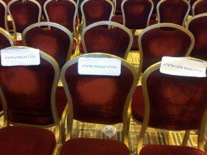 מעדיפים לשבת בצד של הבמה. הכיסאות הריקים של הרבנים שלא הגיעו