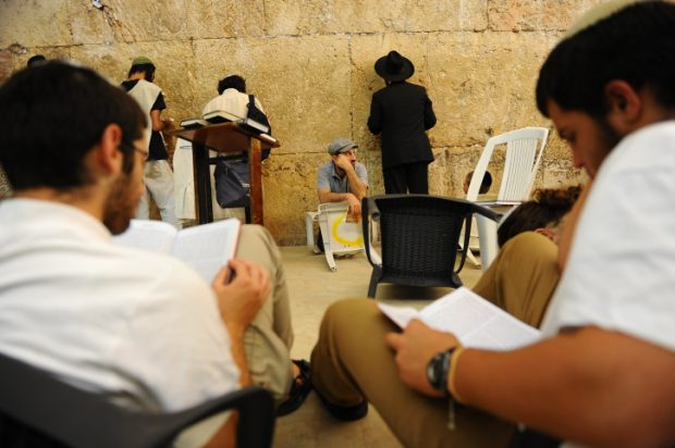 Orthdox Jews men pray as they gather for the ritual of Tisha B'Av at the Wall Western in the Old City of Jerusalem, July 25, 2015. The Tisha B'Av ceremony, literally the ninth day of the month of Av in the Hebraic calendar, is the darkest day in the Jewish calendar, marking the destruction of the two temples, first by the Babylonians in 587 BC and later by the Romans in 70 AD. Photo by Mendy Hechtman/Flash90.   *** Local Caption *** ????? ???? ???? ??? ?????? ?????