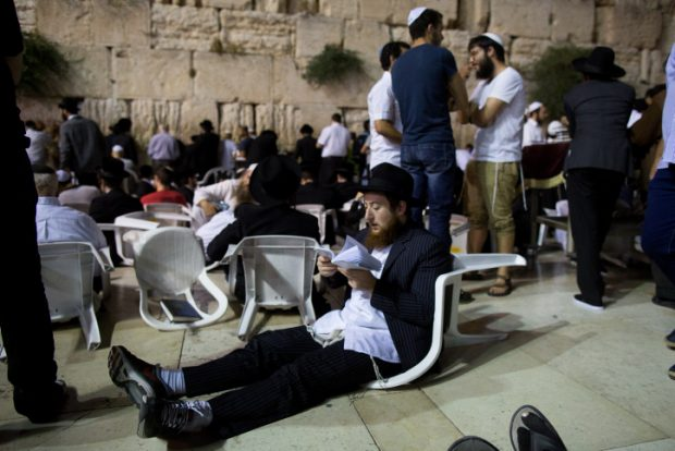 Orthdox Jews men pray as they gather for the ritual of Tisha B'Av at the Wall Western in the Old City of Jerusalem, July 25, 2015. The Tisha B'Av ceremony, literally the ninth day of the month of Av in the Hebraic calendar, is the darkest day in the Jewish calendar, marking the destruction of the two temples, first by the Babylonians in 587 BC and later by the Romans in 70 AD. Photo by Yonatan Sindel/Flash90.   *** Local Caption *** ????? ???? ???? ??? ?????? ?????
