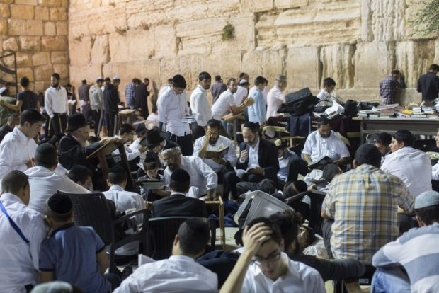 Orthdox Jews men pray as they gather for the ritual of Tisha B'Av at the Wall Western in the Old City of Jerusalem, early on July 26, 2015. The Tisha B'Av ceremony, literally the ninth day of the month of Av in the Hebraic calendar, is the darkest day in the Jewish calendar, marking the destruction of the two temples, first by the Babylonians in 587 BC and later by the Romans in 70 AD. Photo by Yonatan Sindel/Flash90.   *** Local Caption *** ????? ???? ???? ??? ?????? ?????