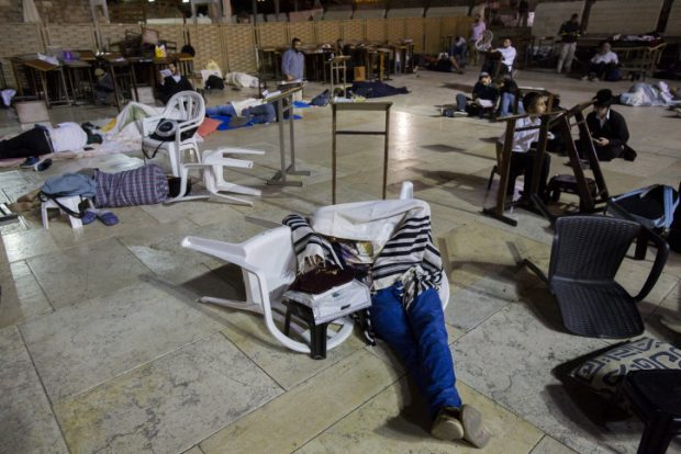 A man sleeps during the ritual prayer of Tisha B'Av at the Wall Western in the Old City of Jerusalem, early on July 26, 2015. The Tisha B'Av ceremony, literally the ninth day of the month of Av in the Hebraic calendar, is the darkest day in the Jewish calendar, marking the destruction of the two temples, first by the Babylonians in 587 BC and later by the Romans in 70 AD. Photo by Yonatan Sindel/Flash90.   *** Local Caption *** ????? ???? ???? ??? ?????? ????? ???? ??? ????