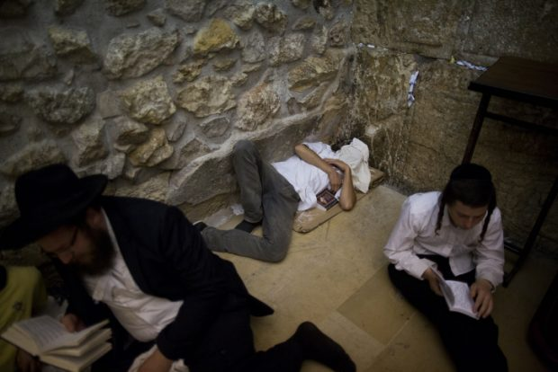An Orthodox jewish man (C) sleeps during the ritual prayer of Tisha B'Av at the Wall Western in the Old City of Jerusalem, early on July 26, 2015. The Tisha B'Av ceremony, literally the ninth day of the month of Av in the Hebraic calendar, is the darkest day in the Jewish calendar, marking the destruction of the two temples, first by the Babylonians in 587 BC and later by the Romans in 70 AD. Photo by Yonatan Sindel/Flash90.   *** Local Caption *** ????? ???? ???? ??? ?????? ????? ???? ??? ????