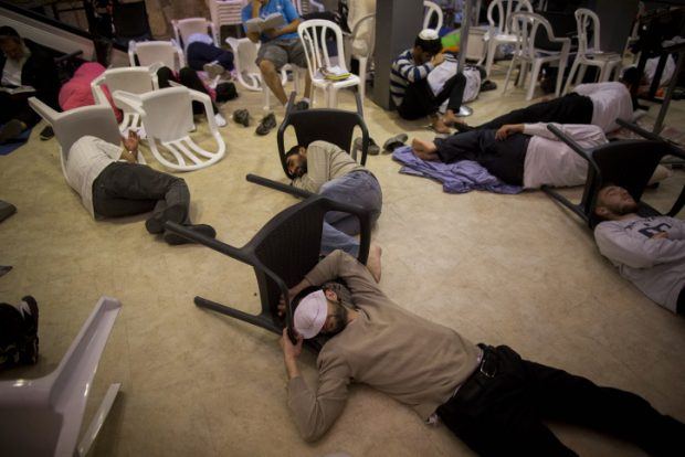 Orthodox jewish men sleep during the ritual prayer of Tisha B'Av at the Wall Western in the Old City of Jerusalem, early on July 26, 2015. The Tisha B'Av ceremony, literally the ninth day of the month of Av in the Hebraic calendar, is the darkest day in the Jewish calendar, marking the destruction of the two temples, first by the Babylonians in 587 BC and later by the Romans in 70 AD. Photo by Yonatan Sindel/Flash90.   *** Local Caption *** ????? ???? ???? ??? ?????? ????? ???? ??? ????