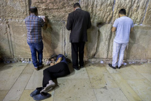 An Orthodox jewish man sleeps during the ritual prayer of Tisha B'Av at the Wall Western in the Old City of Jerusalem, early on July 26, 2015. The Tisha B'Av ceremony, literally the ninth day of the month of Av in the Hebraic calendar, is the darkest day in the Jewish calendar, marking the destruction of the two temples, first by the Babylonians in 587 BC and later by the Romans in 70 AD. Photo by Yonatan Sindel/Flash90.   *** Local Caption *** ????? ???? ???? ??? ?????? ????? ???? ??? ????